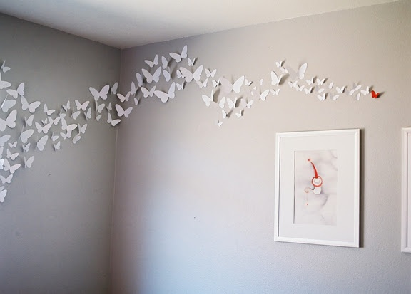Grey wall with white butterflies... and, how perfect, one red one ...