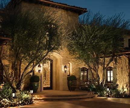use a mix of landscape lights and wall lights to illuminate your home at night