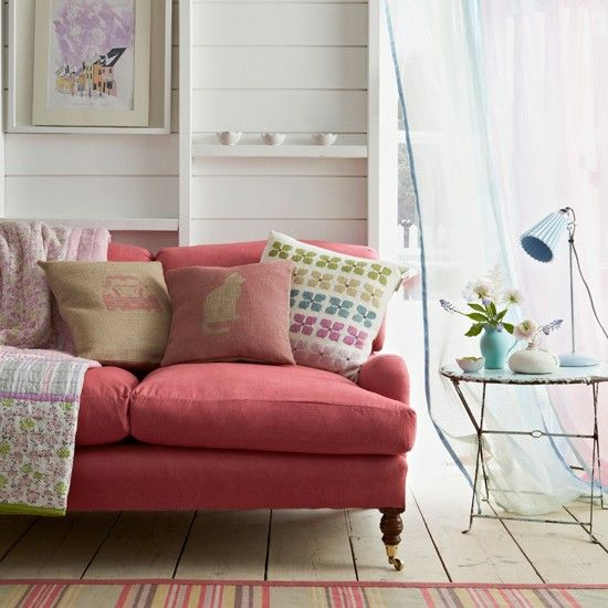 Now here's a decorating idea to chase away the winter blues. Tonal pastel voiles on the window create a soft rainbow effect, while the sofa, in a darker shade of pink, is complemented by the striped rug.
