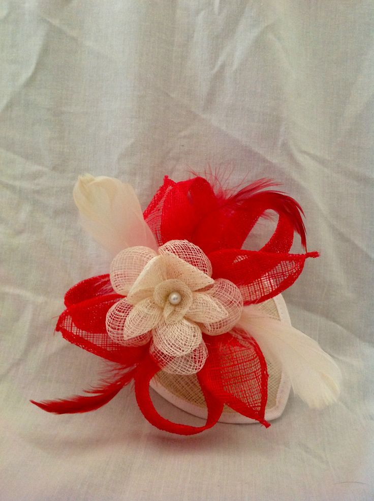 The Summer is a medium fascinator on a tear drop sinamay base with a comb the centre piece is a large buttermilk sinamay flower with pearl detailing surronded by ruby red sinamay loops and leaves with matching feathers to finish. $85 AUD.
