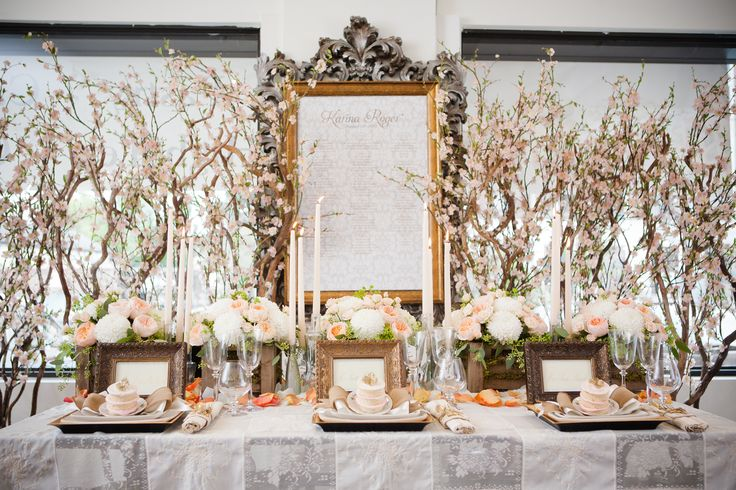 Table Design with Large Cherry Blossom Tree Back Drop.Lush Ivory and Peach Floral Arrangements with Tall Ivory Candles