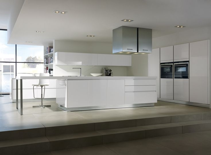 Pure White Themes German Kitchen Design Inspirations with Minimalist Flat Shaped White Wall Mounted Kitchen Cabinet and Modern White Kitchen Island complete with the STtool on the White Flooring also Stainless Steel hanging Chimney Accessories