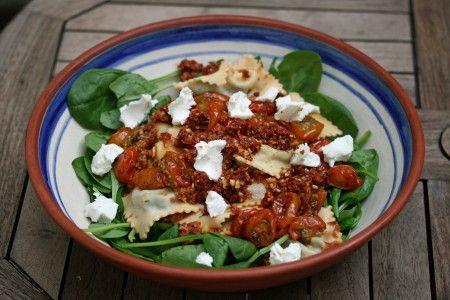 | bereidingstijd 60 minuten | 2-3 personen |  voor de ravioli: • 200 g bloem • 2 eieren • 1 zak verse spinazie van 300 g • 75 g zachte geitenkaas  voor de pesto: • 12 zongedroogde tomaten (eventueel op olie) • 2 teentjes knoflook • een snuf rode pepervlokken • olijfolie • 1 tl verse tijm • 35 gram walnoten of pijnboompitten (licht geroosterd) • 3 handen verse spinazie • eventueel 1/2 bakje cherrytomaatjes, geroosterd in de oven* • 25 g zachte geitenkaas