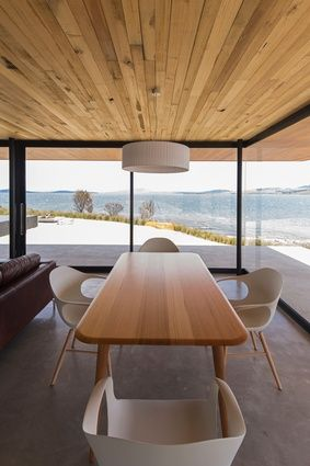 The dining room offers a protective space to watch light play across the bay and landscape.