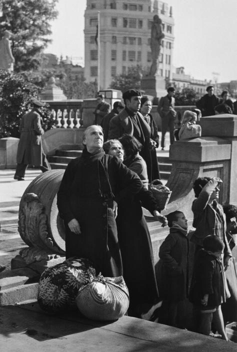 Barcelona, España. Observando una batalla aérea sobre la ciudad, que estaba siendo bombardeada duramente por aviones fascistas, ya que las tropas del general Franco se acercaban rápidamente (entraron en la ciudad el 26 de Enero de 1939). Robert Capa, Enero de 1939.