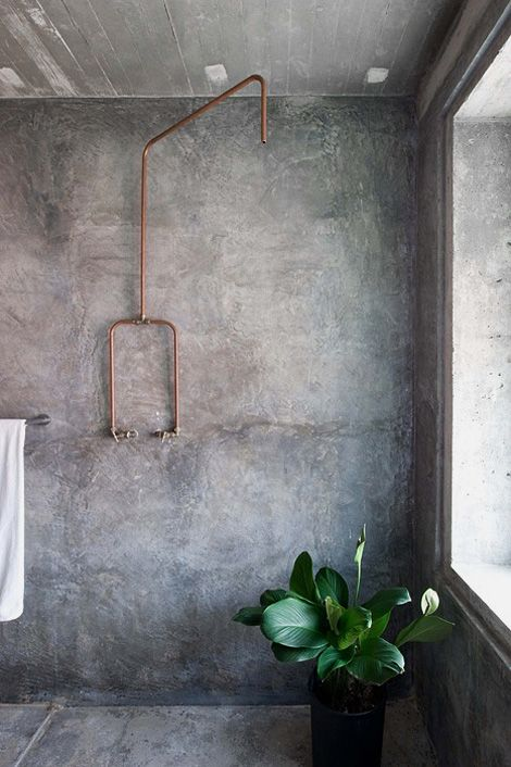 """Exposed copper shower in the concrete bathroom of architect couple Wen Hsia and BC Ang, owners of Building Bloc architecture practice based in Kuala Lumpur."""