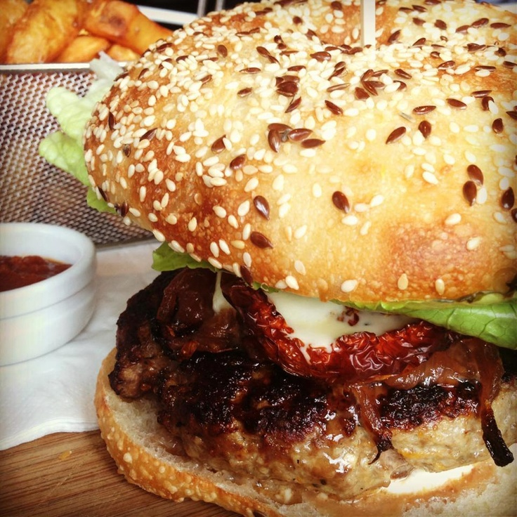 The Common Man #burger features a wagyu patty, roast tomato, onion jam, mozzarella & cos on a seeded Turkish bun. Served with fat chips, it's just the thing for Friday lunch! #swpromenade #melbourne #bar