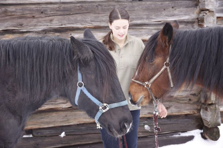 Synne wearing her Moss wool shirt from Hovden Formal Farm Wear while making sure her horses are well. Etsy.