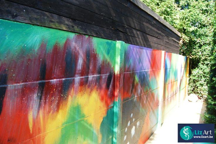 Abstracte muurschildering met felle kleuren in de tuin