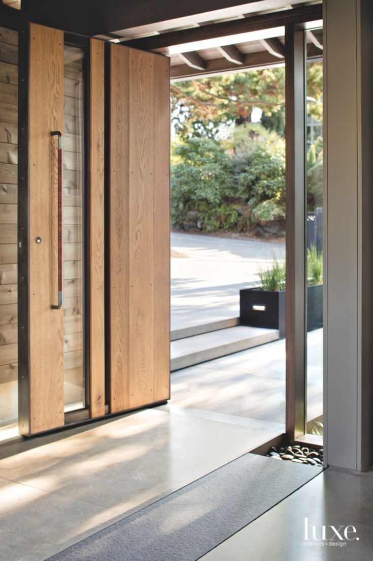 A massive pivot door made of oak, metal and glass, with a steel frame by Architectural Elements, opens to the entry. The home's contractor, Dave Boone, handled the door's woodwork and installation.