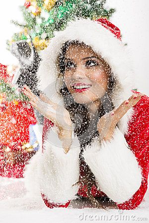 Lovely excited young woman dressed in Santa Claus outfit looking up and enjoying the heavy falling snow while lying on the ground. Studio shot.