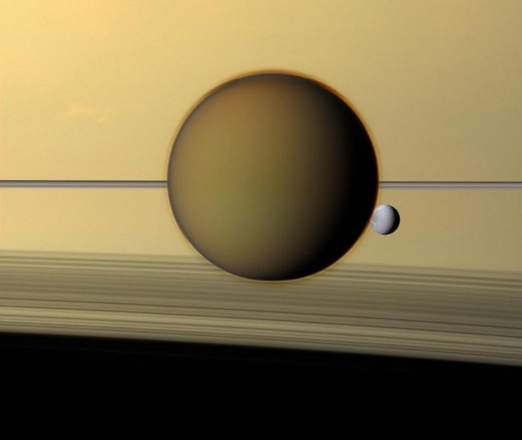 The scene features Titan, largest, and Dione, third largest moon of Saturn.  Pale Dione is about 1,100 kilometers across and orbits over 300,000 kilometers from the visible outer edge of the A ring. At 5,150 kilometers across, Titan is about 2.3 million kilometers from Cassini, while Dione is 3.2 million kilometers away.