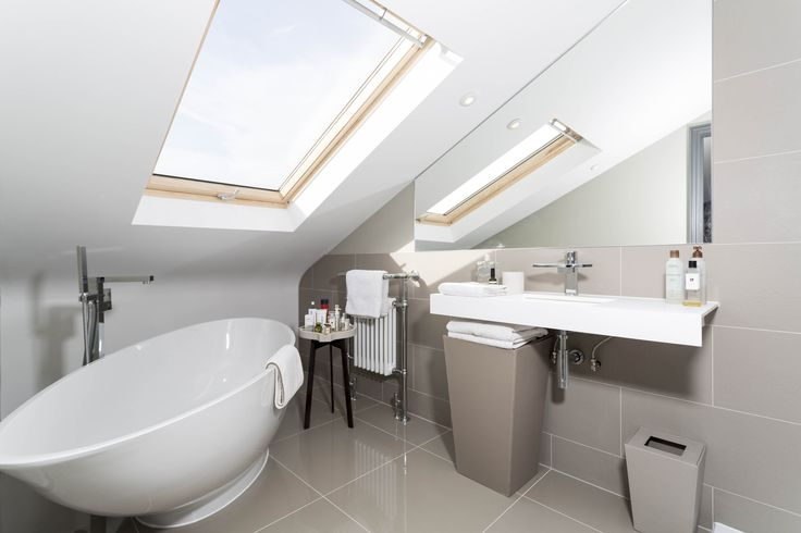 Grey tiled loft conversion bathroom with beautiful free standing bath. Constructed by Simply Loft, London's leading loft conversion specialist.