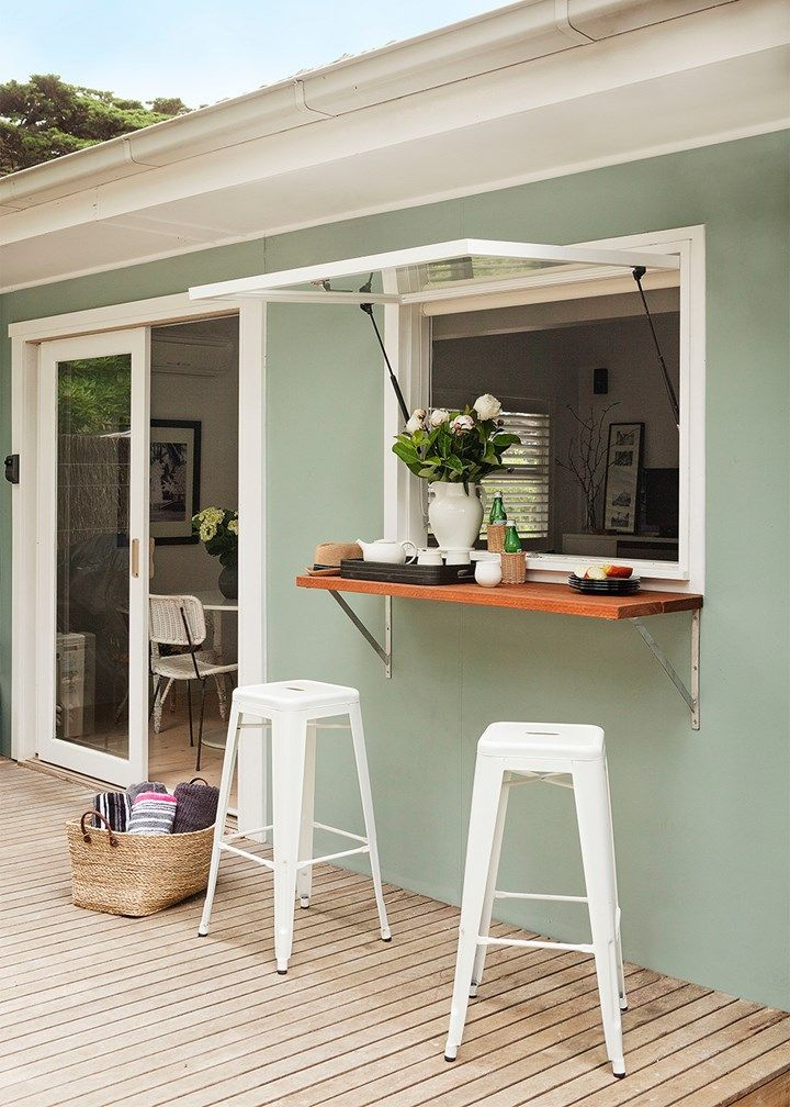 Stunning seaside renovation | The divine teal green exterior is actually a relic of the original house which was refreshed by painting the door and window frames white to match a pair of replica Tolix stools in front of the kitchen window. The deck was extended to create a larger entertaining area, flanked by greenery.