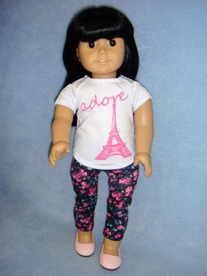 """Paris Top is white knit w/pink graphic, short-sleeved & Velcro fastener down the back. Floral Knit Leggings have elastic waist. Fits 18"""" girl dolls such as American Girl & Springfield Collection. Shown with 2 3/4"""" Pink Slip On Shoes (66487) (not included)."""