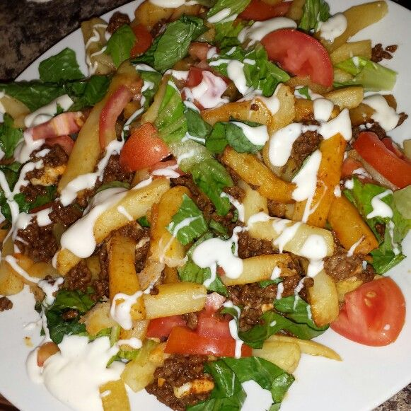 Taco sald poutine. Fries, ground chicken cooked with taco seasoning,   tomato, lettuce,  and a mayo/ranch mix dressing