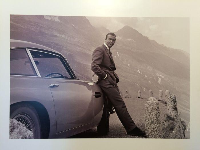 James Bond in Aston Martin DB 5-60 x 80 cm 45 x 66 cm zonder marge. 340 gram fotopapier  Foto van Sean Connery in Goldfinger.Deze foto werd gemaakt op de Furkapas (Stelvio) tijdens de filmopnamen van Goldfinger.Op de Furkapas stopt James Bond.Bond volgde Tilly Masterson in haar Ford Mustang. De Mustang raakt ernstig gewond deur de blikopeners van de Aston Martin...Afmetingen: 60 x 80 cm 45 x 66 cm zonder marge. 340 gram fotopapier.In uitstekende staat.  EUR 30.00  Meer informatie