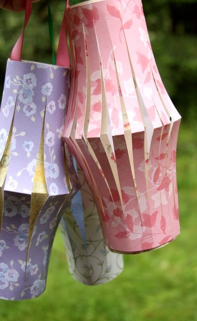 Make Paper Lanterns. 2 pieces of scrapbooking paper, on hand  Scrap of ribbon, on hand  Scissors and clear tape, on hand