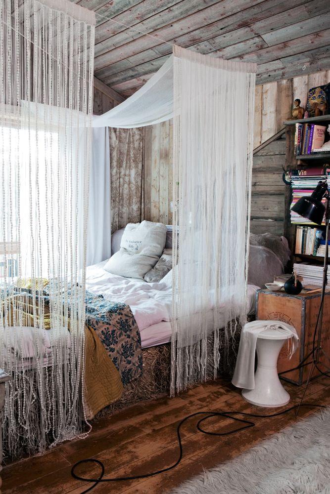 """En halmsäng? """"Ja, vi ville ha en säng man kan ligga i på alla håll, så vi tillverkade en av halmbalar och lade en futonmadrass ovanpå."""" Även gaveln är i halm, fast tygklädd. Sänghimlen är gjord av pärljalusier och tunn väv. Överkast och tyska mjölsäckskuddar, vintage. Svart golvlampa, containerfynd. Nattygsbordet var från början full med te, köpt i Berlin. Den mönstrade sidengardinen i fönstret har följt Ingvild sedan ungdomen."""