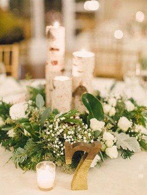 A rustic winter wedding centerpiece with birch candle holders and pine decorations.