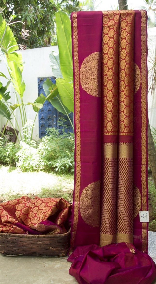 This sari is a traditional kanchivaram in reddish orange with a symmetrical pattern woven in gold zari all across. The border is in magenta with a spaced out pattern in gold zari, while the pallu h...