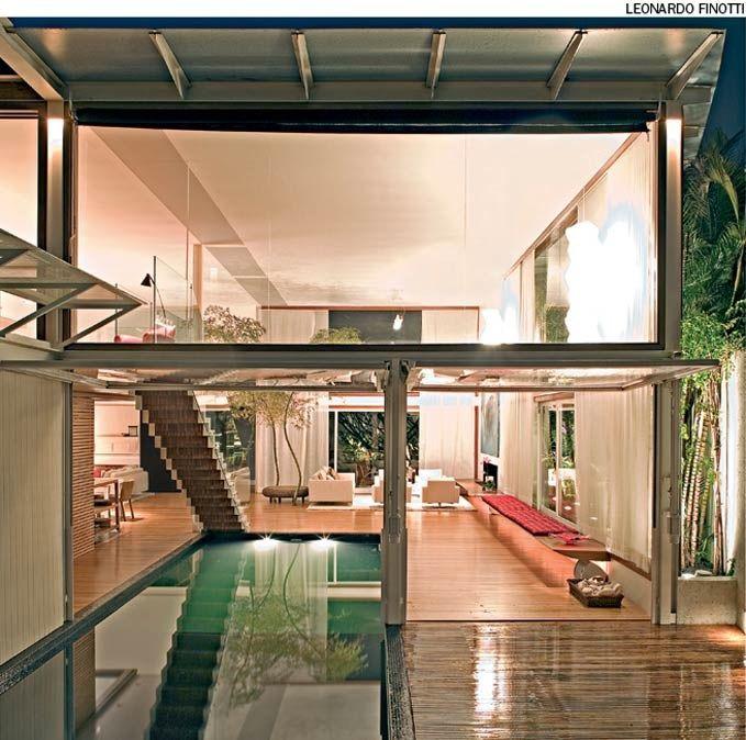 Portas basculantes abrem totalmente o living para a área externa. A da esquerda fica em cima da piscina que entra no ambiente. A parte alta, acima da viga de aço, é fechada por painéis de vidro fixo. Projeto do escritório Bernardes Jacobsen.