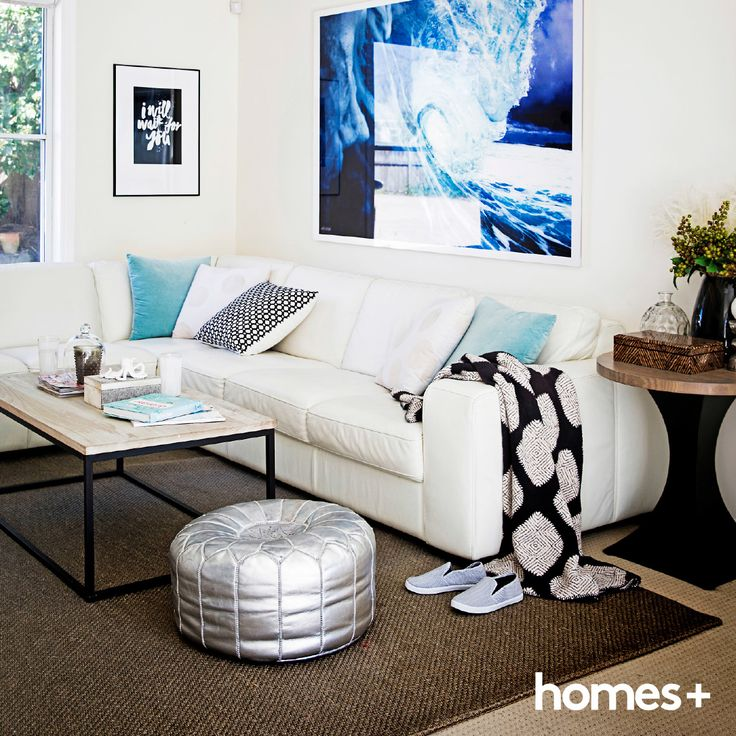 Jacyln styled her white #living #room with cool #blues and touches of #silver. As featured in the April 2015 issue of homes+. #sofa #pouf #coffee #table #cushions #artwork #print #rug #decor #style #interior #beachhouse #homesplusmag