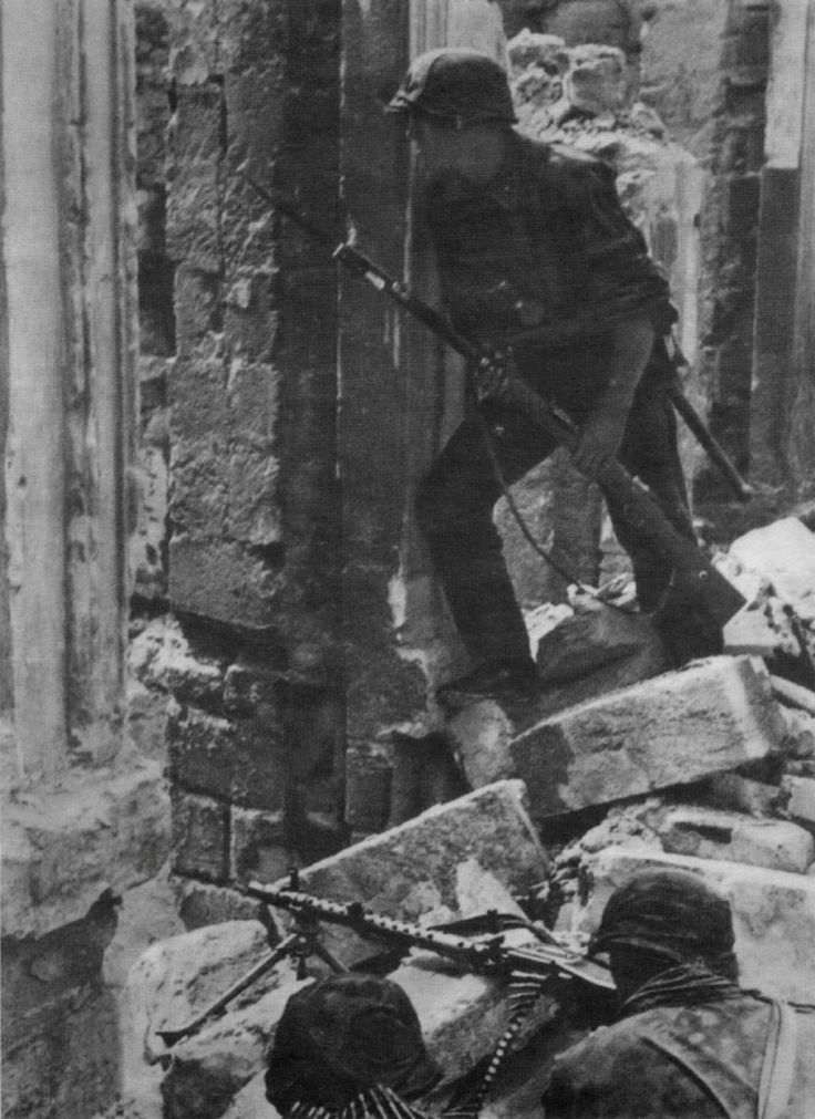 """A machine gun element of  SS-Division """"Leibstandarte Adolf Hitler"""" take positions in the ruins during street fighting in Mariupol, Ukraine, Oct 1941. The city was overrun on Oct 8 and remained in German hands until Sep 10, 1943."""