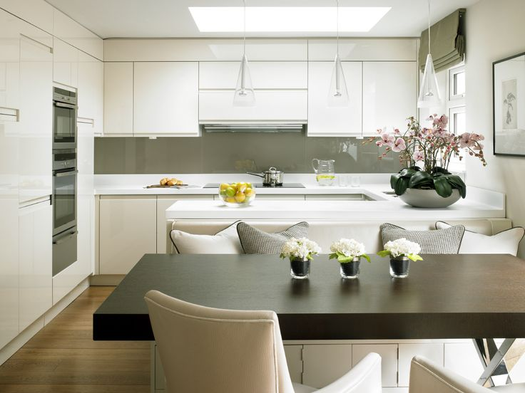 contemporary kitchen with gloss lacquer cabinets, Corian worktop and dark wood table