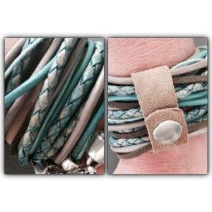 Wikkelarmband met verschillende soorten materiaal en kleuren dat bij elkaar gehouden wordt door een strookje leer.