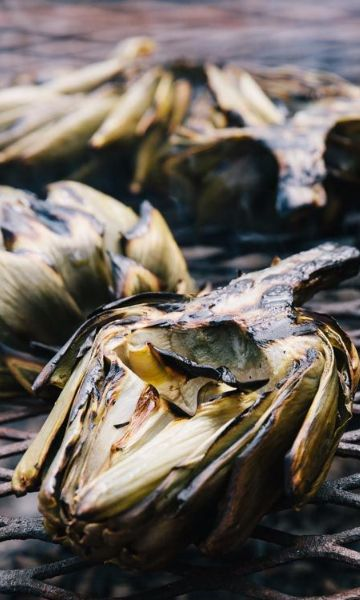Artichokes are fibrous and difficult to cook down into a chewy texture. But with this recipe, most of the preparation is done in advance, leaving just a brief sear over high heat to finish—perfect for while you're waiting for the fire to die down.