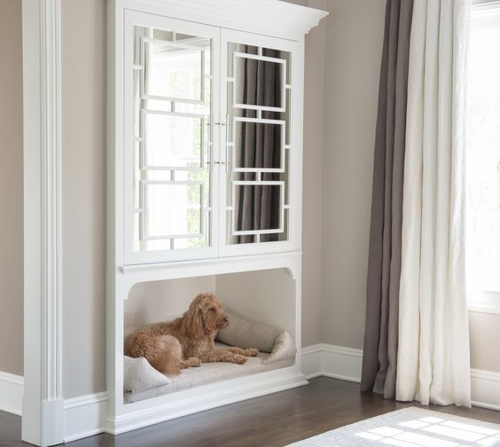 Warm light gray bedroom walls frame built in mirrored cabinets positioned over an inset dog bed positioned on a wall adjacent to a window covered with gray and white pleated curtains.