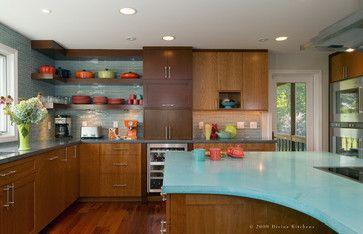水色のカウンタートップやバックスプラッシュにオレンジの食器が映える。