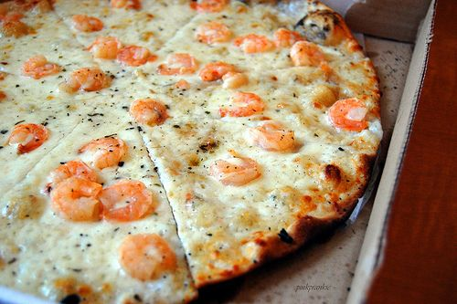 Witte Garnalen Pizza: dikke bechamelsaus met knoflook (en kruiden?), witte gekarameliseerde ui, garnalen in knoflook, peper, zout, knoflookolie/peperolie, rucola of spinazie