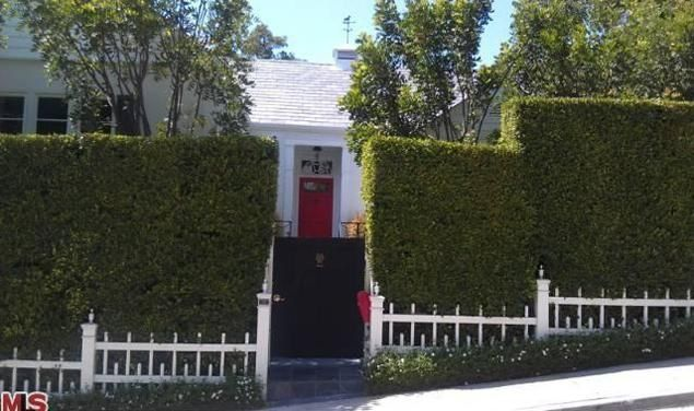 The exterior of the home, constructed in 1952, is behind privacy hedges.