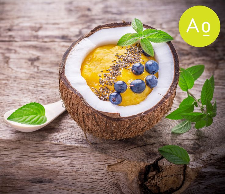Mango smoothie garnished with chia seeds in the shell of a coconut with berries, blueberries and mint leaves.