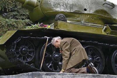"""A Russian war veteran kneels beside the tank he spent the war in, now a monument."""