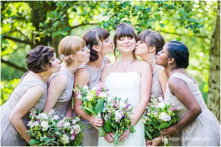 Bridesmaids kissing bride