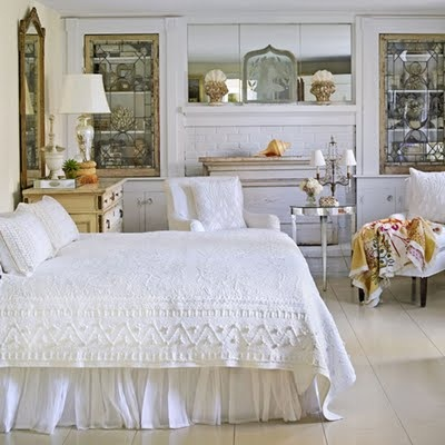 Crisp white lace bedding, lighting fixtures with white shades, stained glass cabinet doors, and antique mirrors above a white fireplace all come together to create the dreamiest of bedroom designs.