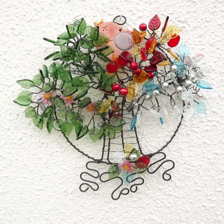 Ptačí strom 6. - Čtvero ročních období Drátovaný ptačí strom - je drátovaný z černého železného drátu a skleněných lístečků zelené, žluté, oranžové, bílé,hnědé a červenébarvy, červených a stříbrnýchvoskových perliček, keramického ptáčka od Acxl a vinutých skleněných květů od Ivanký Hujerové. Průměr kolečka - podkladu je 16 cm, průměr ...