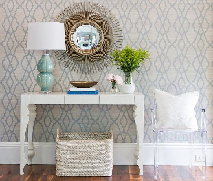 Chic foyer features a wall clad in gray and blue trellis wallpaper lined with a white console table with curvy legs topped with a blue lamp under a gold starburst mirror next to a Ghost Chair.