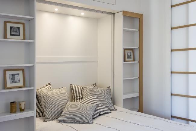 Chambre avec murs bibliothèque blancs. Cousins rayés blancs et gris.