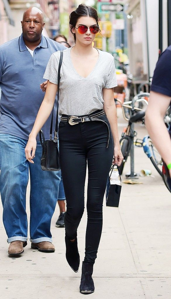Kendall Jenner pairs her booties with a grey v-neck, high-waisted black jeans, and a black crossbody bag.