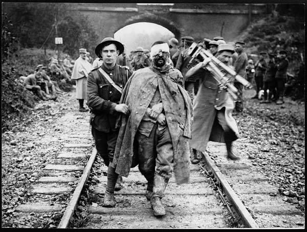 Boche prisoner wounded and muddy coming in on the 13th (1918) A British soldier is helping a wounded German prisoner walk along a railway track away from a bridge. A man possibly in French military uniform is shown behind them holding a camera and tripod.  The derogatory term for a German 'Boche or 'Bosch originates from the French slang 'alboche which was two words 'Allemand (German) and 'caboche (pate head) put together. This photograph is a reminder that the French also had official war…