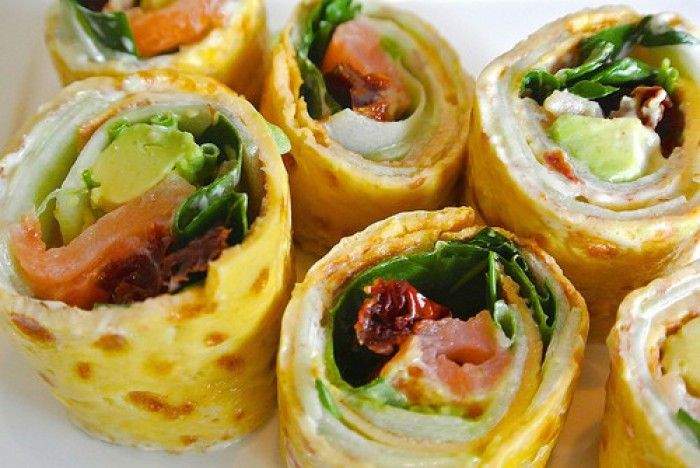 tapas amuse hapjes: omelet-rolletjes met zalm, avocado en gedroogd tomaatjes.