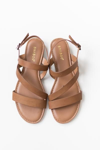 """Tan flat sandals with a strappy faux leather upper Small .75"""" back heel Buckle closure around ankle Lightly padded insole True to US size All man made material"""