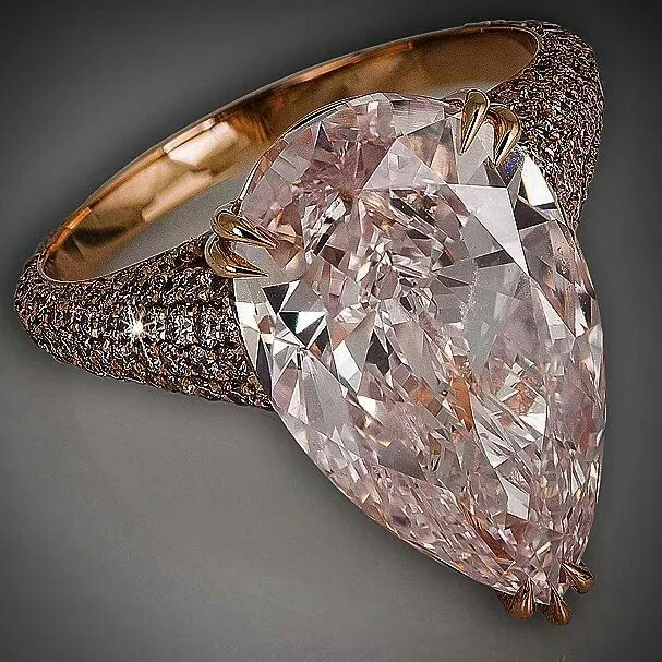 David Morris ring featuring a pear shaped 8.06ct Fancy pink diamond surrounded by a band of pink diamonds