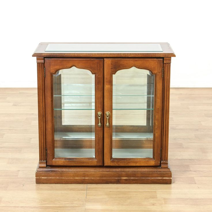 This small display case is featured in a solid wood with a glossy cherry finish. This cabinet has clear glass sides, an interior cabinet with shelving and a mirror back. Great for displaying accessories and collections! #americantraditional #storage #displaycabinet #sandiegovintage #vintagefurniture