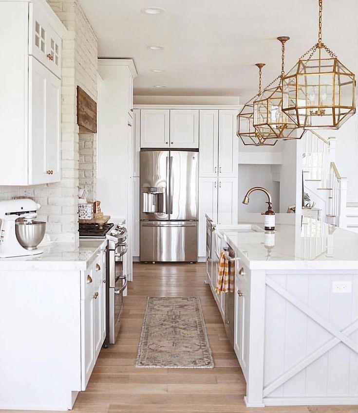 Gorgeous white kitchen with gold light fixtures.