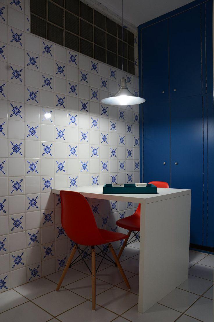 Revestimento antigo foi mantido em apartamento em Porto Alegre. O antigo armário em fórmica foi adesivado de azul e as cadeiras Emas Wood vermelhas trazem vida ao ambiente.